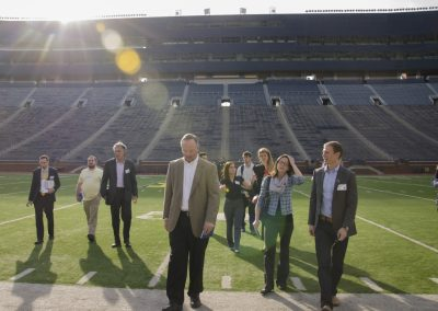 """U-M Injury Center Sport Concussion attendees on the field during a tour of """"The Big House"""""""