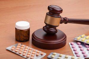 Pills surrounding a gavel
